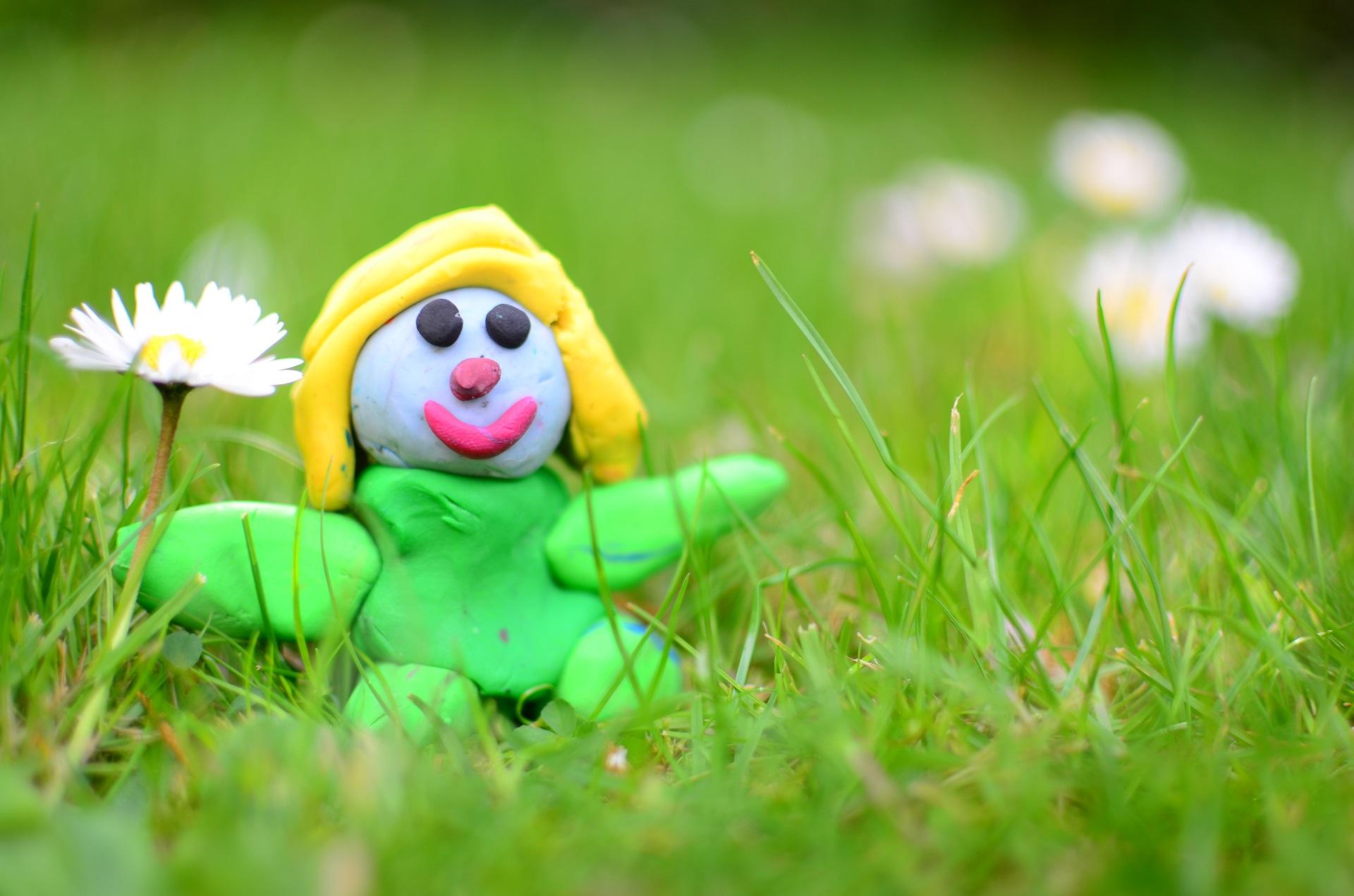 Clay model of Emma sitting amongst flowers