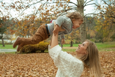 Parent playing with her child lifting him into the air